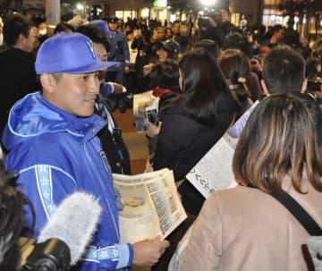 自らの新主将就任の号外を配るDeNAの佐野(手前左)=25日、横浜市