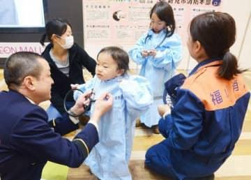 感染防護服を試着する女児ら