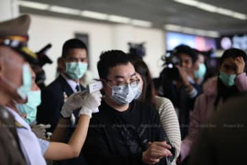 A man is scanned for a fever at Don Mueang airport on Saturday. (Photo by Apichart Jinakul)