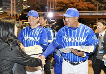 本紙号外を配るラミレス監督(右)と佐野=JR桜木町駅前