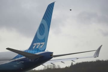 A Boeing 777X airplane taxis for the first flight, which had to be rescheduled due to weather, but the company will try again Saturday.