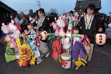 晴れ着姿で花桶をかついで練り歩く女児たち=25日午後5時、小山市寒川