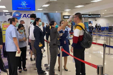 An official uses a thermoscanner to check whether a passenger has a fever at Chiang Mai airport on Friday. (Photo supplied by Cheewin Sattha)