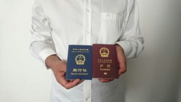 An unidentified Chinese Uighur man in the city of Medina holds his expired Chinese passport (red) and a one-way travel document (blue) issued in its place by the Chinese mission in Saudi Arabia. (AFP photo)