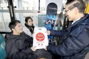 記念品を受け取る妙高高原ライナーの乗客=25日、上越市の上越妙高駅