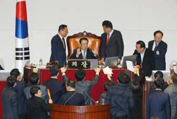 法案処理を巡り野党議員の抗議を受ける韓国国会の文喜相議長(奥左から2人目)=2019年12月、ソウル(聯合=共同)