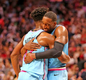 The Miami Heat's Jimmy Butler, left, and Bam Adebayo hug after defeating the Indiana Pacers, 113-112, at the AmericanAirlines Arena in Miami on December 27, 2019. - CHARLES TRAINOR JR/Miami Herald/TNS