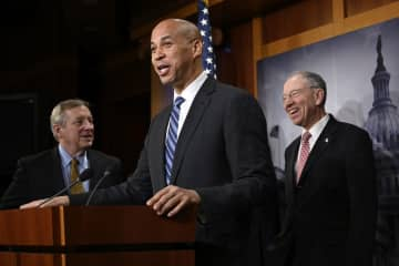 Sen. Cory Booker, D-N.J., center, flanked by Sen. Dick Durbin, D-Ill., left, and Sen. Chuck Grassley, R-Iowa, right, speaks during a news conference after the First Step Act was signed into law in December. (AP Photo | Susan Walsh) (Susan Walsh/)