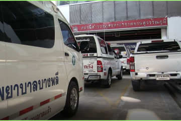 An ambulance and pickup trucks of social workers is seen in front of the Suvarnabhumi police station on Sunday to pick up the body of a Belgian man who was found dead in the detention cell there. (Photo supplied by Sutthiwit Chayutworakan)