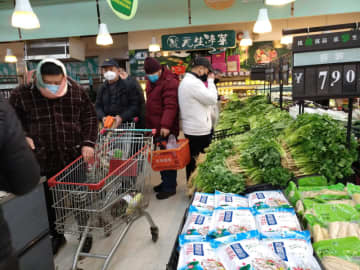 People wearing masks shop at a supermarket on the second day of the Chinese Lunar New Year, following the outbreak of a new coronavirus, in Wuhan, Hubei province, on Sunday. (Reuters photo)