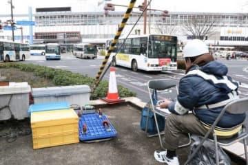 カウンターを使ってバスの通過台数などを調べる調査員