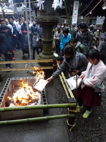 感謝を込めて使い古した筆や半紙などを火に投げ入れた参拝者=座間神社