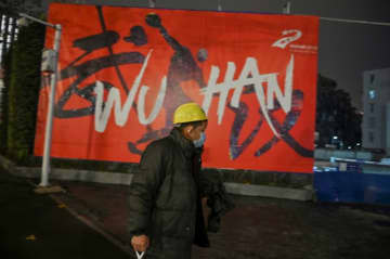 A man wearing a protective facemask walks along a street in Wuhan on January 26, 2020, a city at the epicentre of a viral outbreak that has killed at least 56 people and infected nearly 2,000.