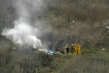 Firefighters work the scene of a helicopter crash where former NBA star Kobe Bryant died, Sunday, Jan. 26, 2020, in Calabasas, Calif. (AP Photo/Mark J. Terrill) (Mark J. Terrill/)