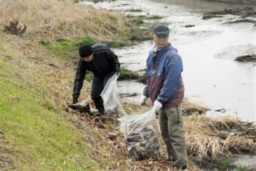熊本城マラソンのコース沿道や土手などのごみを拾う銭塘校区の住民たち=熊本市南区