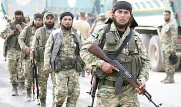 Turkey-backed Syrian fighters walk near the Turkish village of Akcakale along the border with Syria, as they prepare to take part in the Turkish-led assault on northeastern Syria.