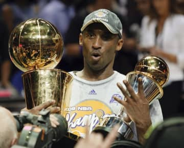 In this June 14, 2009 file photo Los Angeles Lakers' Kobe Bryant holds the Larry O'Brien championship trophy and finals MVP trophy after the Lakers defeated the Orlando Magic 99-86 in Game 5 of the NBA basketball finals in Orlando, Fla.