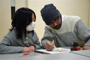 絵画教室で、絵が好きな子どもに指導をする伊藤さん=1月中旬、五所川原
