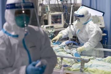 中国・武漢の病院で新型肺炎患者の対応にあたる医療関係者=24日(新華社=共同)