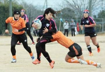ボールを手にトライを目指す熊本チームの選手。紺色が熊本チーム=八代市