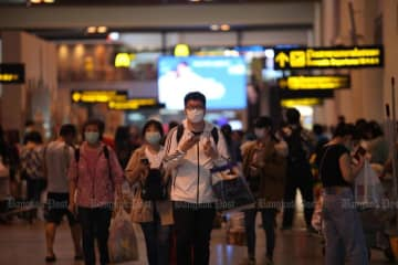 Tourists with face maskes arrive at Don Mueang airport on Saturday. (Photo by Apichart Jinakul)