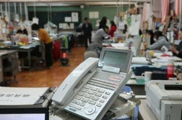 午後7時を回った職員室。電話は自動対応に切り替わったが教員の一部は残り、負担の軽減が課題となっている(京都市右京区・西院小)