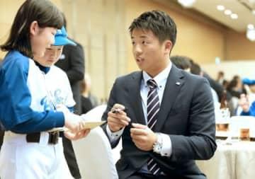 ファンと交流するヤクルトの鈴木裕太投手(右)=25日、新潟市中央区
