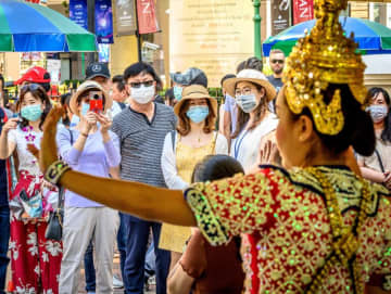 Chinese tourists wearing face masks watch a traditional dance at the Erawan Shrine on Monday. (AFP photo)