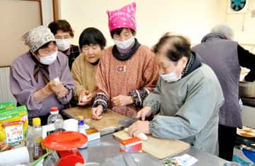小麦粉の生地でギョーザの皮作りに取り組む参加者