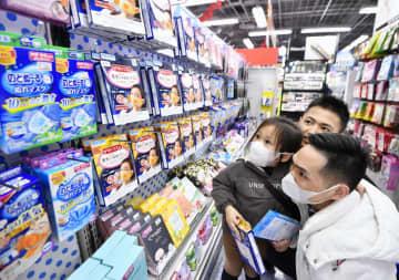 春節の大型連休中に日本を訪れ、マスク売り場で商品を見る中国人観光客。中国では性能の高いマスクは品薄だという=27日午後、東京・秋葉原のヨドバシカメラ