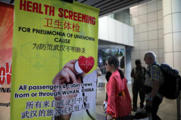 Passengers pass by a banner about Wuhan Pneumonia at thermal screening point at international arrival terminal of Kuala Lumpur International Airport in Sepang, Malaysia, on Tuesday. (Reuters photo)