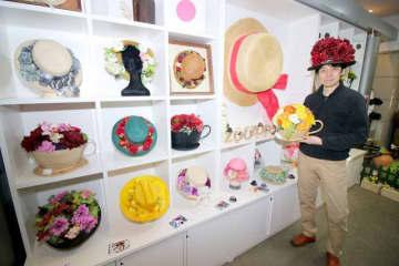 石田製帽の帽子に萬木さん(右)が花を飾り付けた作品が並ぶ会場