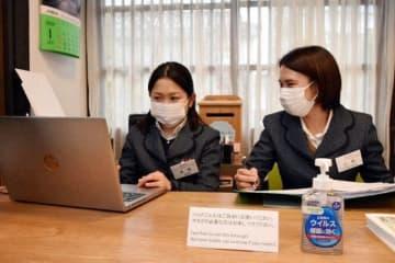 マスクを着けて業務に当たる観光案内所の職員。観光客用に消毒液も用意した=倉敷市美観地区