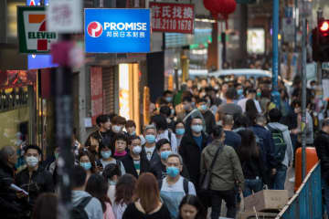 People wearing masks walk on a street in Kwun Tong district of Hong Kong on Thursday. (Bloomberg photo)