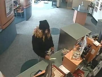 A man who appeared to disguise his appearance with white facial makeup and a shoulder-length wig robbed a Toms River bank on Thursday. (Toms River Police Department/)