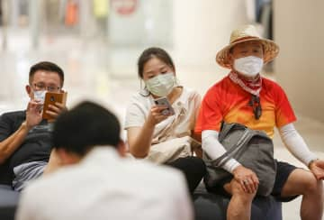 Chinese tourists and shoppers wear masks at a mall. Tourism has been directly harmed by the coronavirus outbreak. PATTARAPONG CHATPATTARASILL