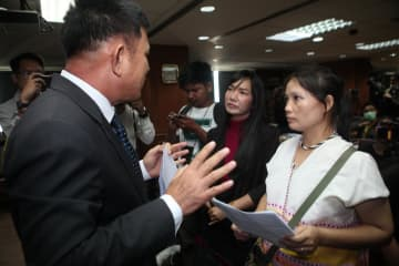 Pinnapa Prueksapan, right, wife of Karen activist Porlajee 'Billy' Rakchongcharoen, asks a prosecutor why murder charges against suspects, including the ex-Kaeng Krachan National Park chief were dropped. Apichart Jinakul