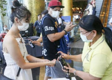 Shoppers receive hand gel before entering the Iconsiam shopping mall on Monday. (Photo by Pattarapong Chatpattarasill)