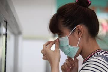 A visitor at the Bamrasnaradura Infectious Diseases Institute wears a germ mask. Photo: Wichan Charoenkiatpakul