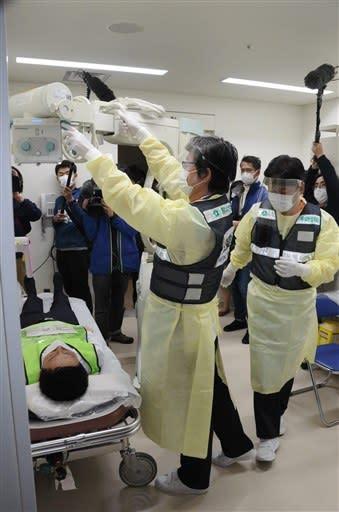 感染予防のためのフェースシールドと防護服姿で、患者役の肺のエックス線検査にあたる放射線技師ら=27日、熊本市東区の熊本市民病院