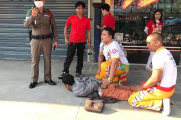 Members of a lion-dance troupe hold Preecha Inna firmly on the ground after catching him after he knocked over an old woman as he fled from a gold shop with two necklaces in Nakhon Sawan's Muang district on Monday. (Photo by Chalit Poomruang)