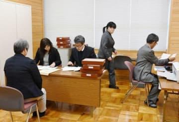 中学校教員(左)から受け取った願書を確認する岡山東商業高の教職員