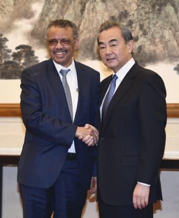 会談前に握手する中国の王毅国務委員兼外相(右)とWHOのテドロス事務局長=28日、北京の釣魚台迎賓館(共同)