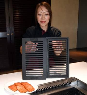 新たに導入した南部鉄器製の鉄板をPRする従業員。肉がふっくらと焼ける