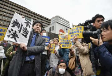大阪地裁の前で「不当判決」と書かれた紙を掲げる弁護士(左端)=28日午後