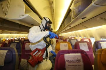 An employee of Thai Airways International sprays disinfectant aboard a plane, during a  demonstration of the airline's sanitary measures to help curb the spread of the novel coronavirus. (Photo by Varuth Hirunyatheb)