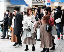記録的な暖かさの中、思わずコートや上着を腕に掛けて過ごす人たち=28日午後、神戸市中央区(撮影・秋山亮太)
