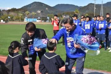花束を受け取り笑顔を見せる三浦知良選手(右)と下平隆宏監督=28日午後、日南市・日南総合運動公園陸上競技場