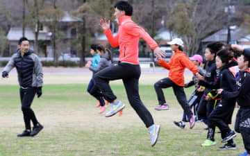 三段跳びの山本(JAL、中央)と里コーチと一緒に基礎トレーニングに励む小中学生=県立総合運動公園補助競技場