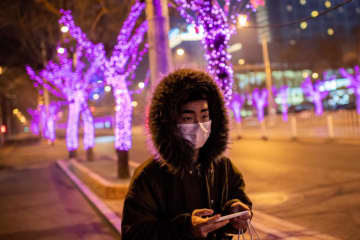 A man wears a protective mask to help stop the spread of a deadly virus, as he walks in a near-empty area of Sanlitun in Beijing on Tuesday. (AFP photo)